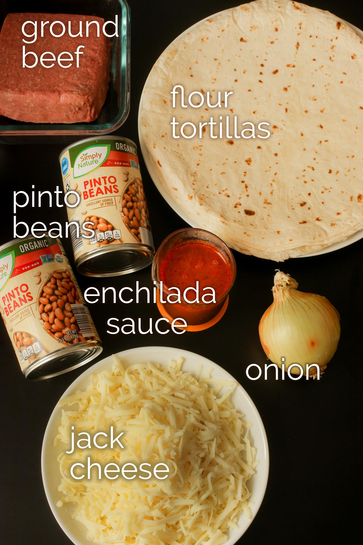 ingredients for bean and beef burritos laid out on black countertop.