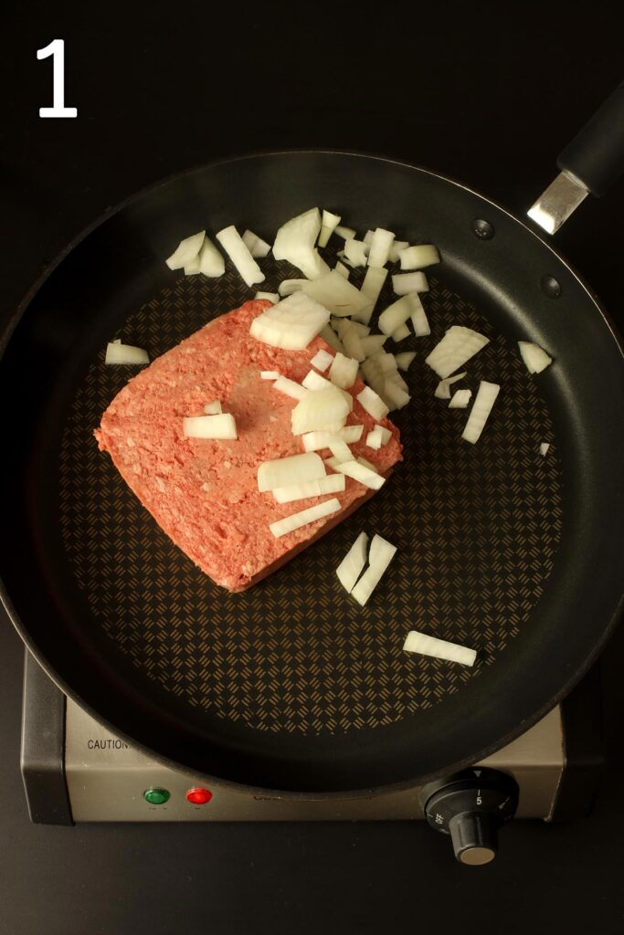 brick of ground beef in skillet with chopped onion.