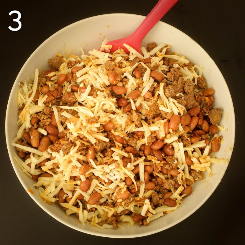 mixing in shredded jack cheese into the bean and beef mixture in white bowl.