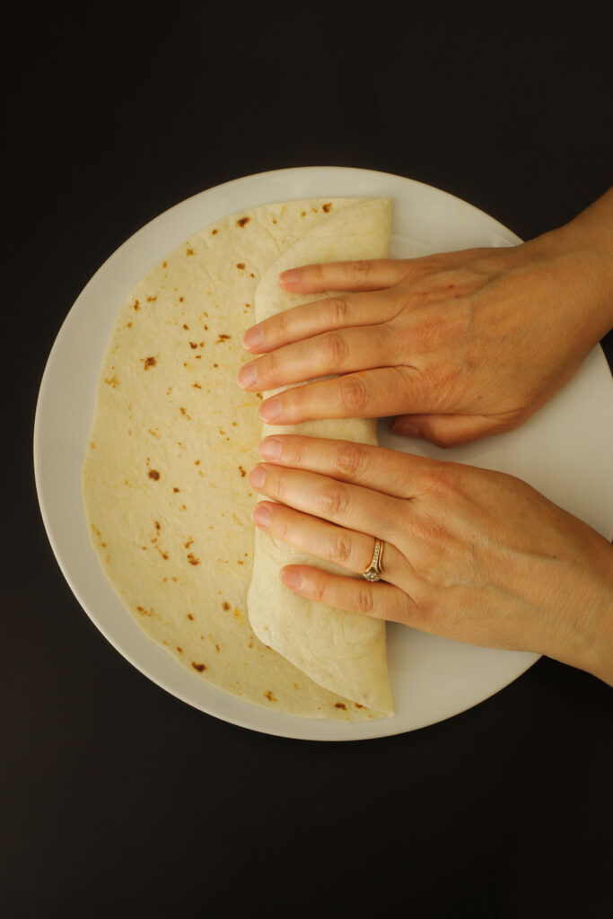 hands rolling one side of tortilla over the filling.