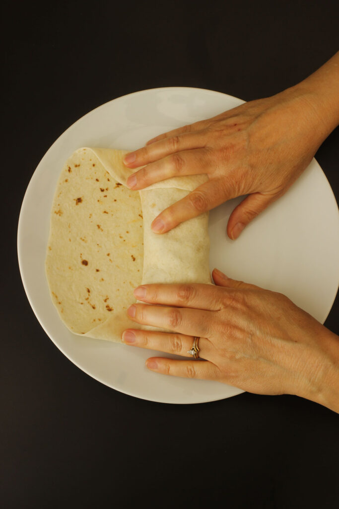 hands folding in sides over the first roll of tortilla.