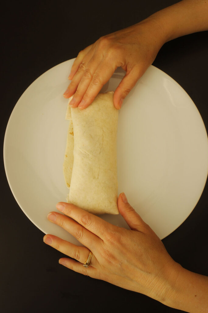 hands holding the rolled burrito on the plate.