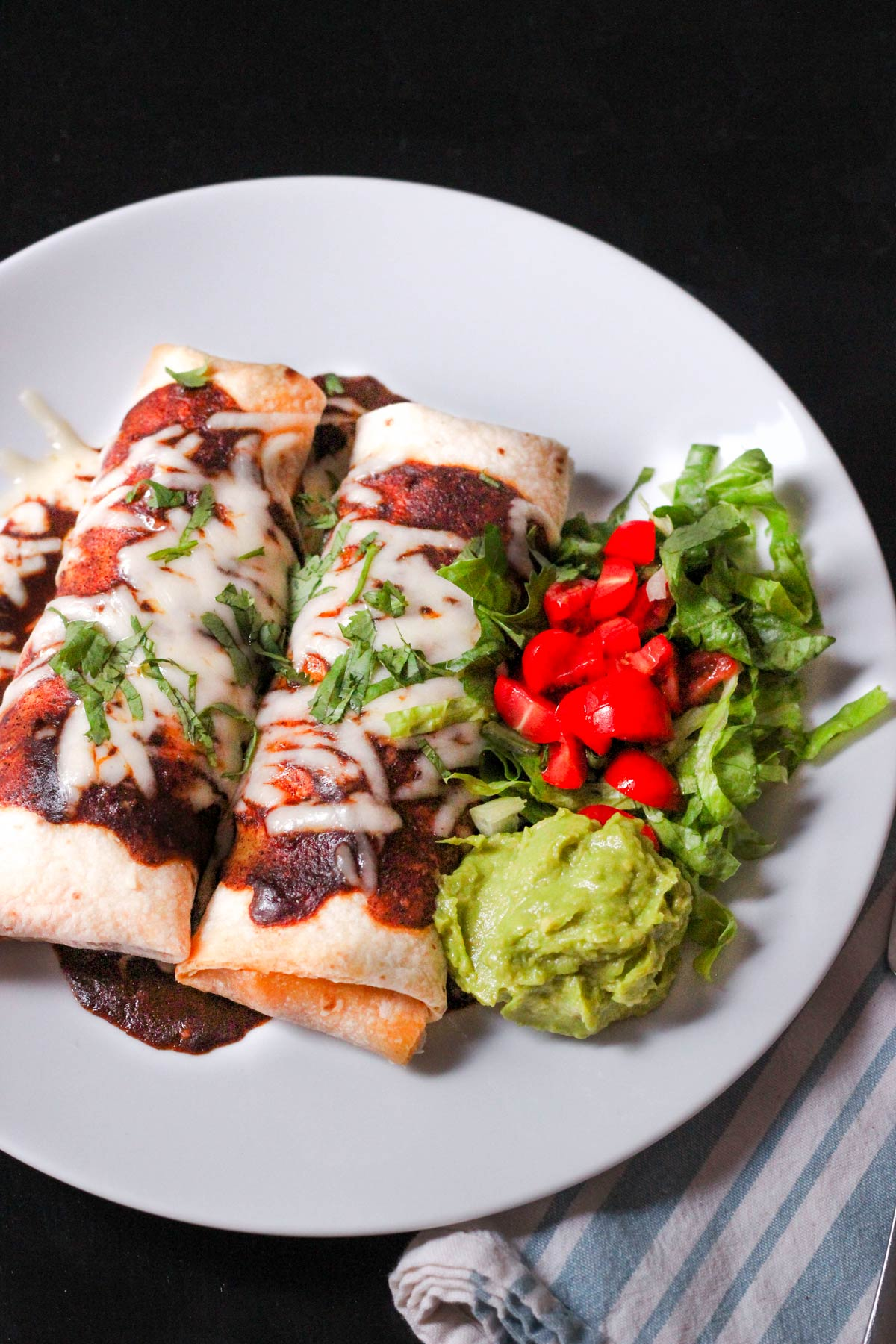 two bean and beef burritos on a plate topped with red sauce and melted cheese with guacamole and salad on the side.