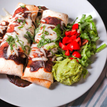 two bean and beef burritos on a white dinner plate topped with sauce, cheese, and cilantro.