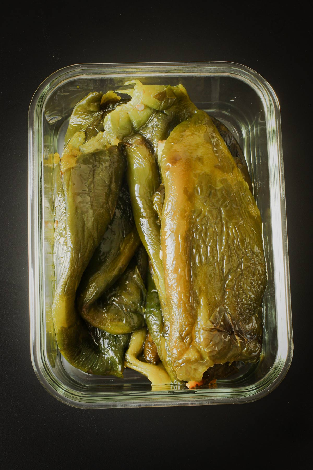 whole roasted poblano peppers in glass dish.