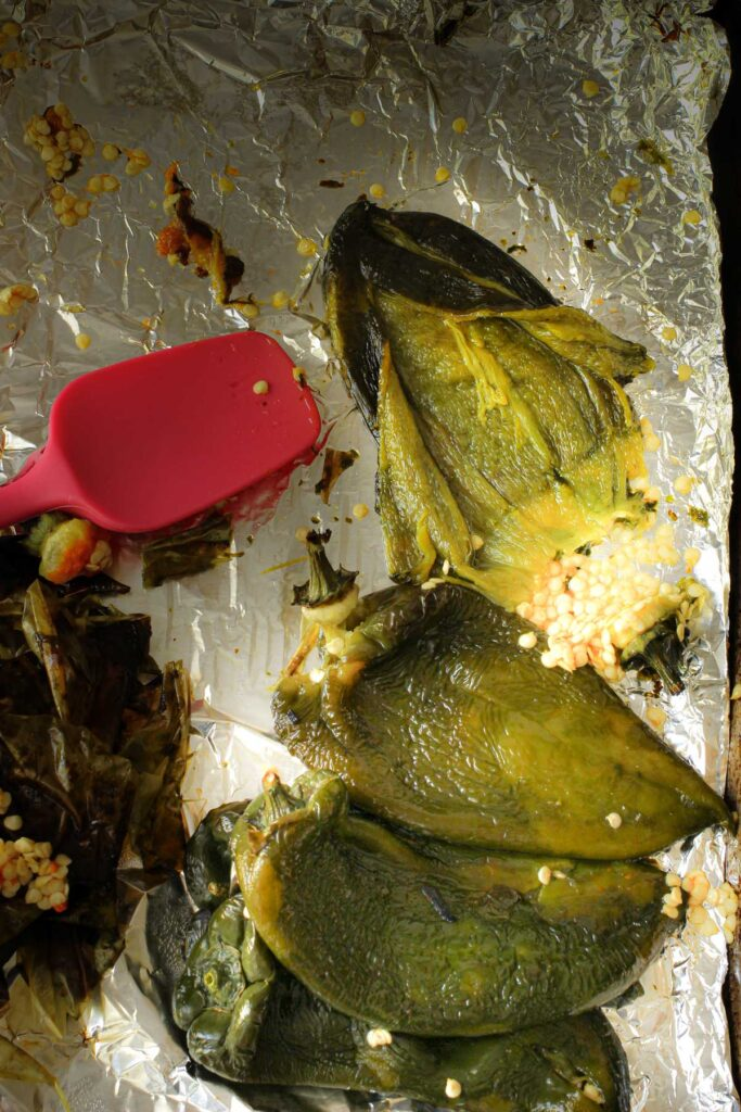splitting open the poblano chile and scraping away the seeds with a rubber spatula.
