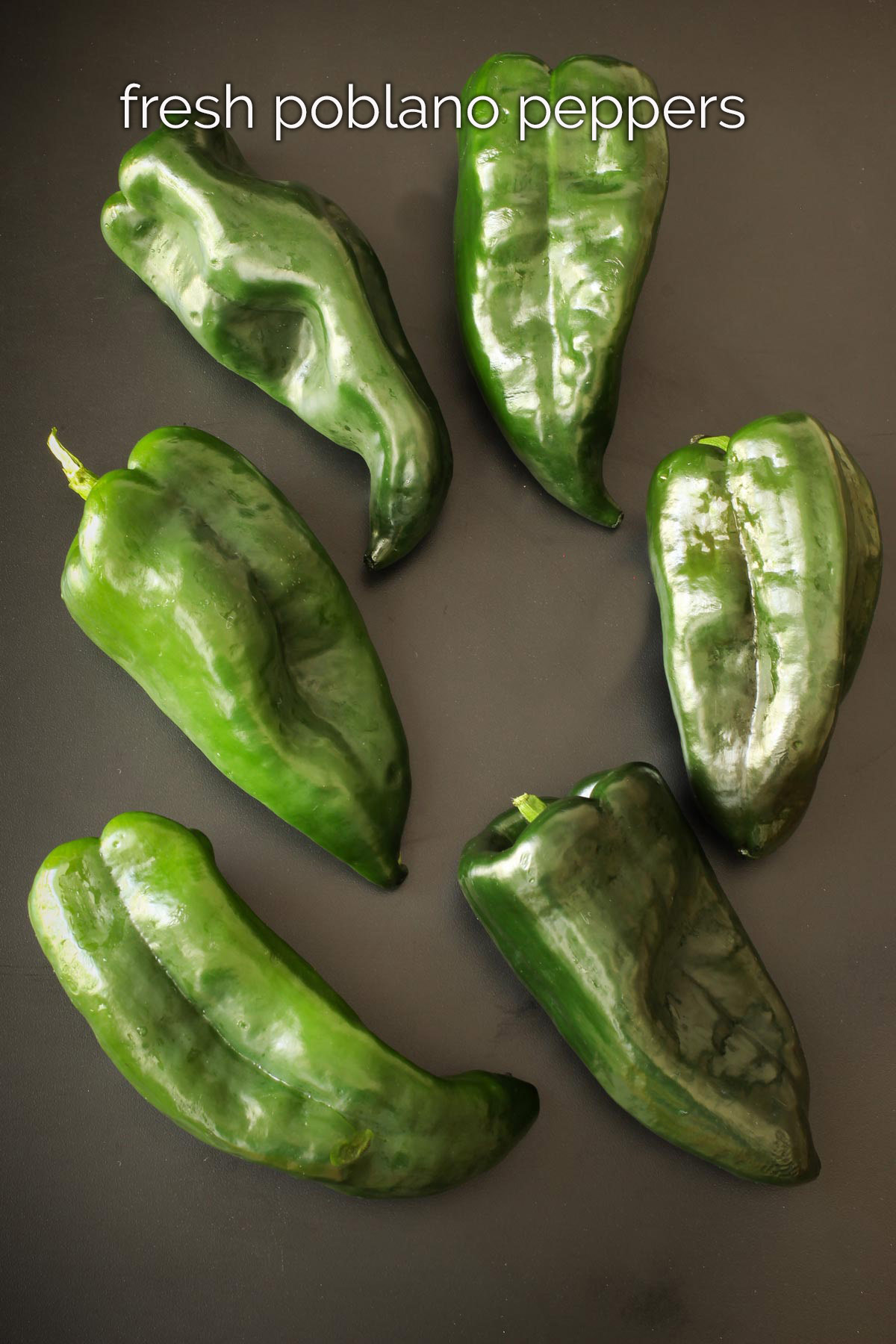 fresh poblano peppers on a black tabletop.