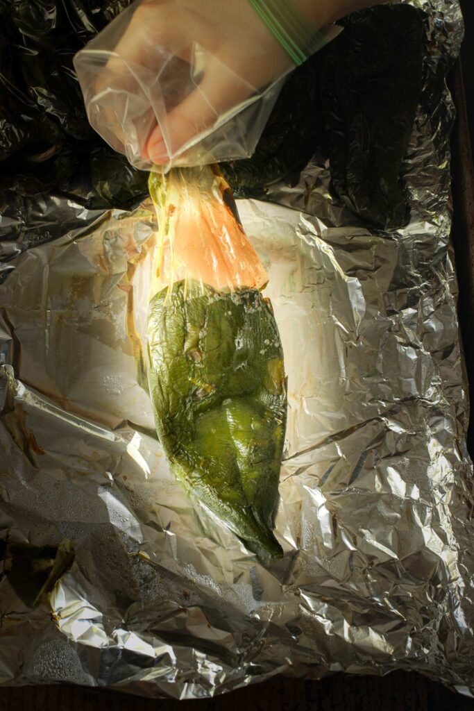 peeling the papery skin away from the roasted poblano pepper.