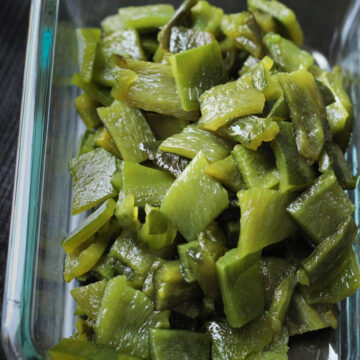 chopped and roasted poblano chiles in a glass dish.