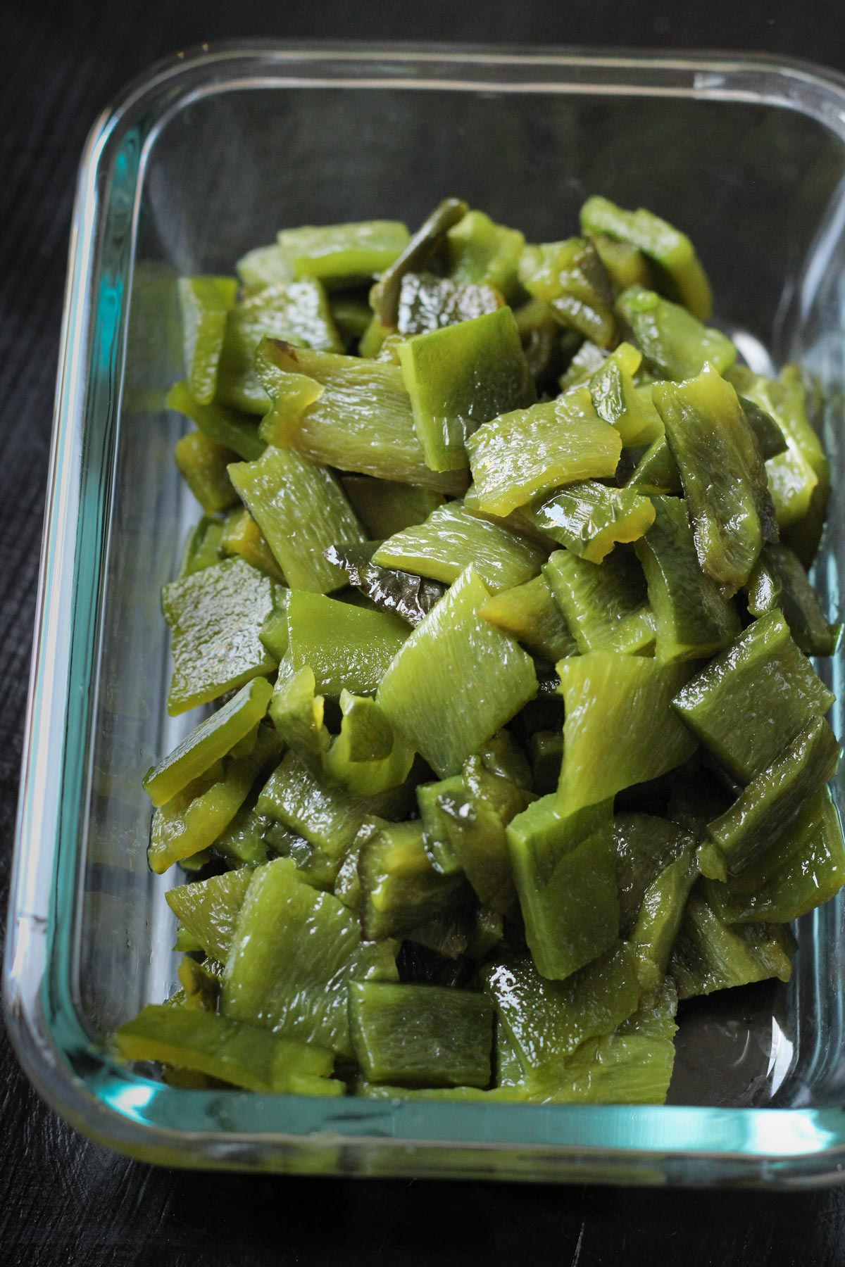 diced and roasted poblano peppers in a glass storage dish.