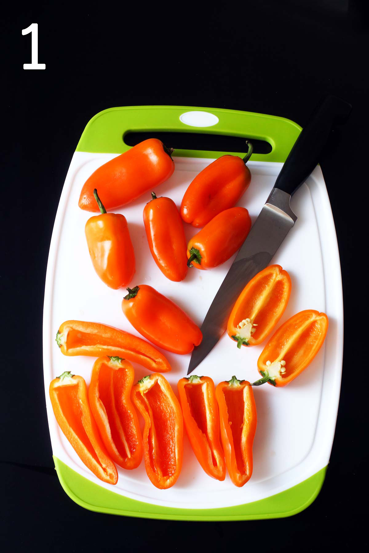 mini peppers on cutting board with knife.