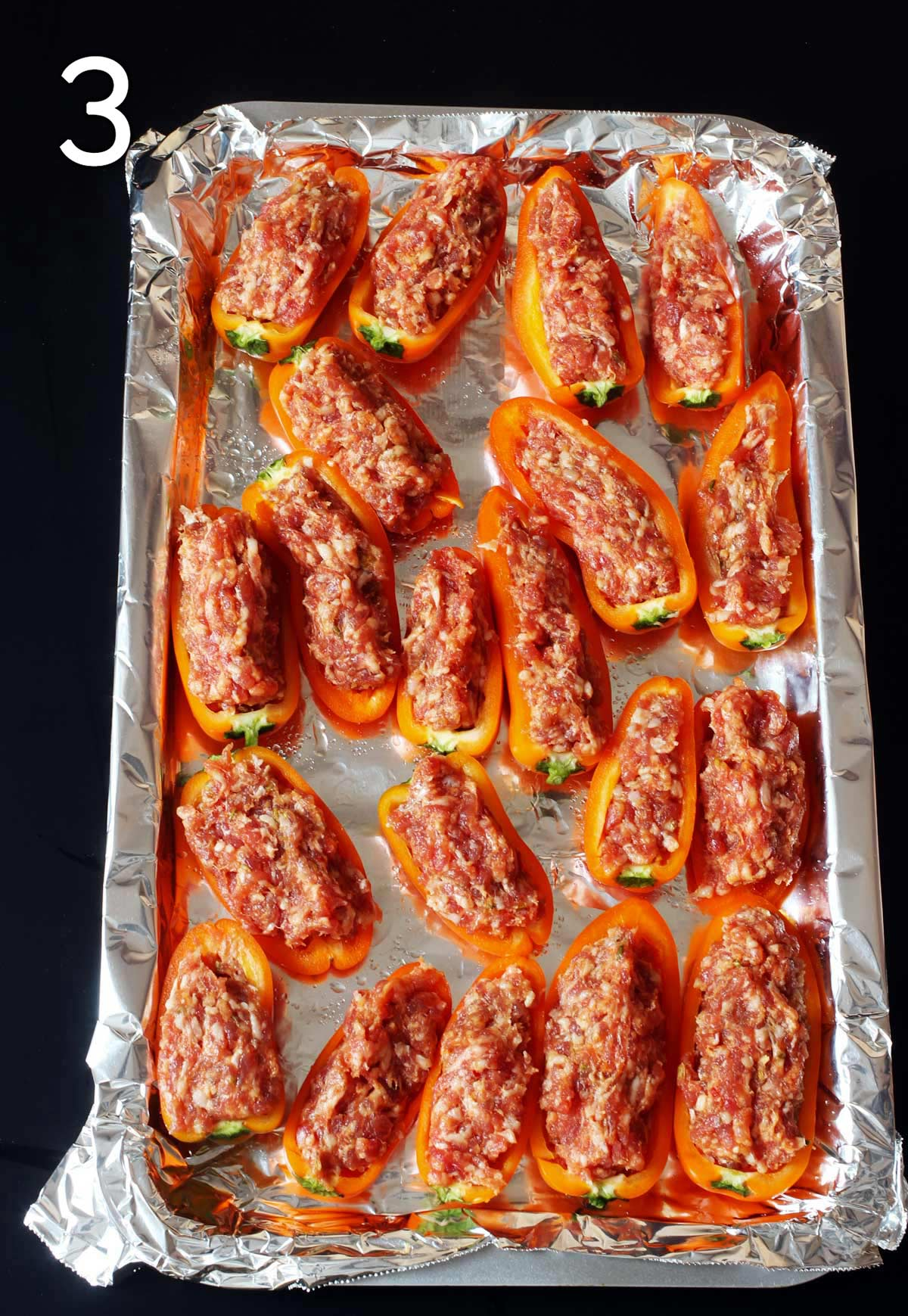 peppers stuffed with uncooked sausage on baking sheet.