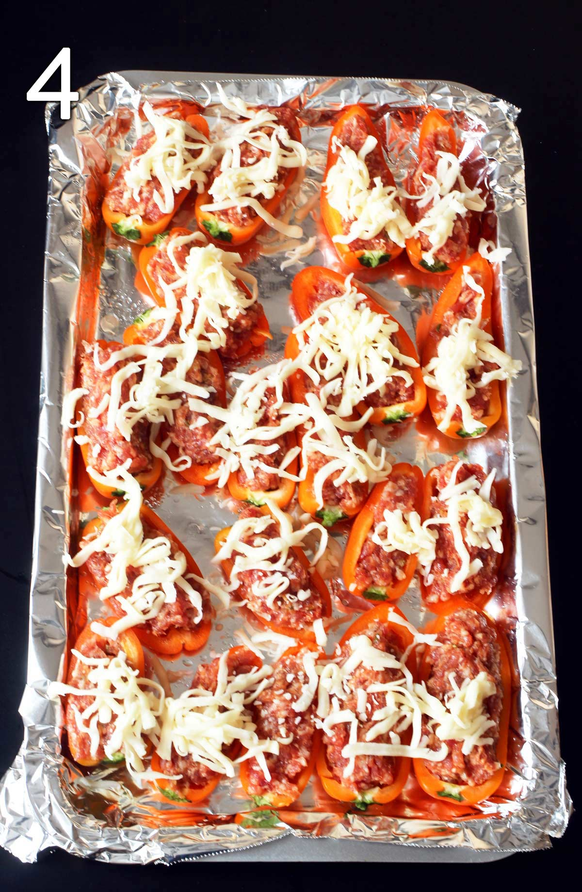 cheese sprinkled over the unbaked peppers on the baking sheet.