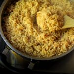 wooden spoon scooping up rice from a pan of seasoned rice pilaf.
