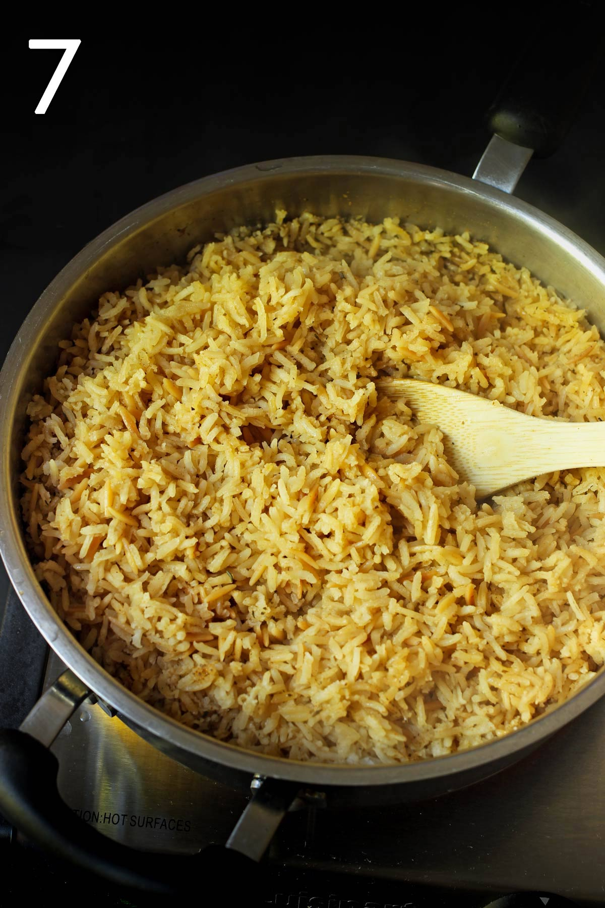cooked rice in the pan with a wooden spoon.