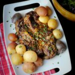 slow cooked chuck roast on platter with herbs and tri-color potatoes.