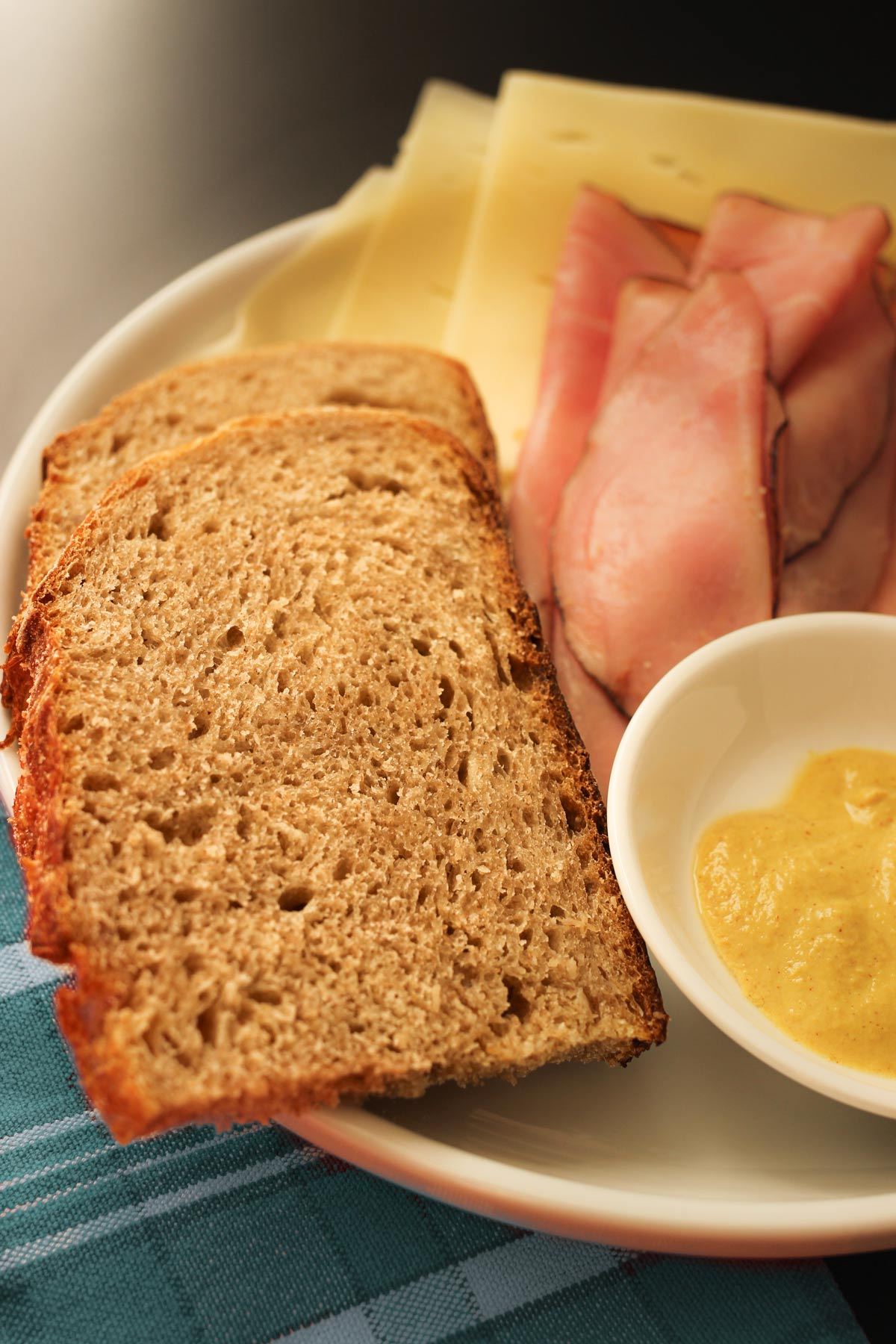 close up of sourdough rye bread on plate with mustard, ham, and swiss cheese.
