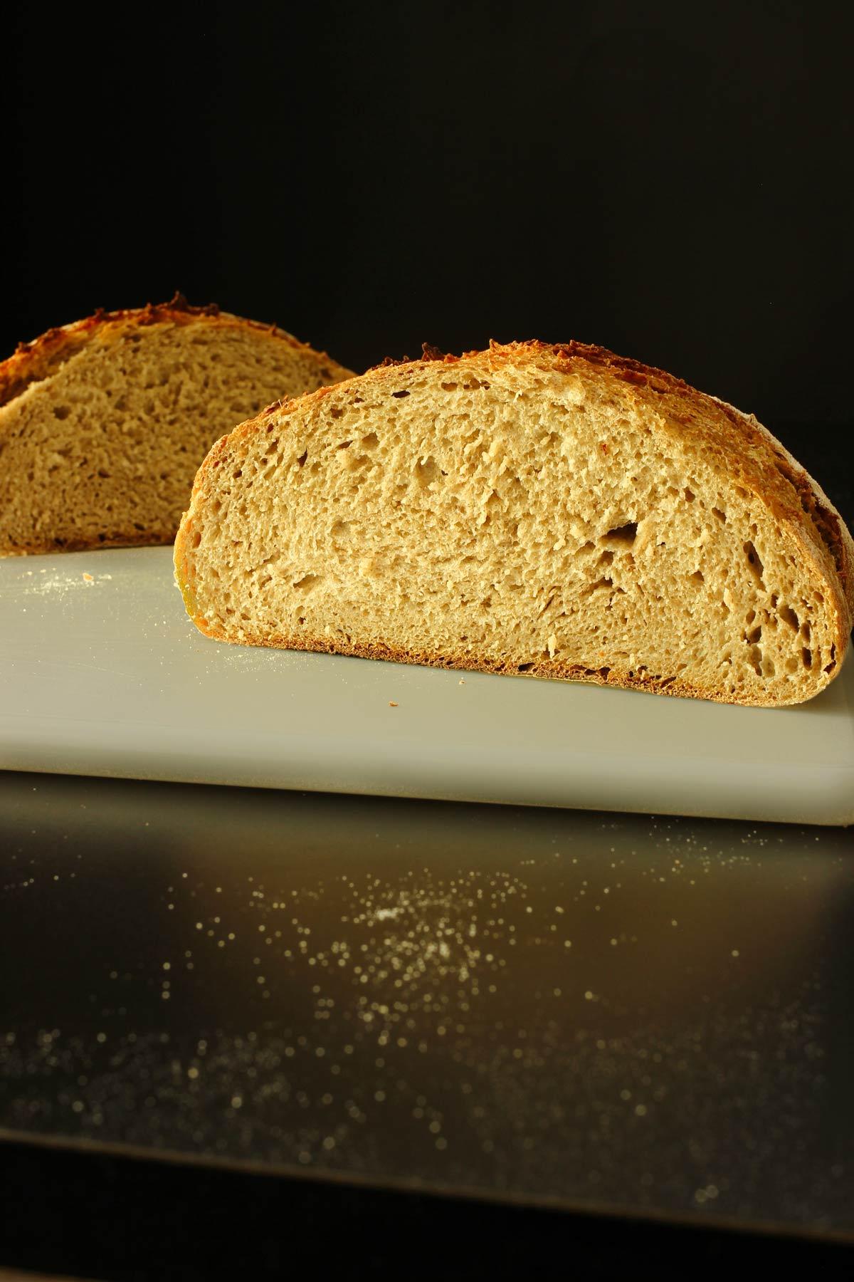 loaf of sourdough rye on the cutting board cut in half.