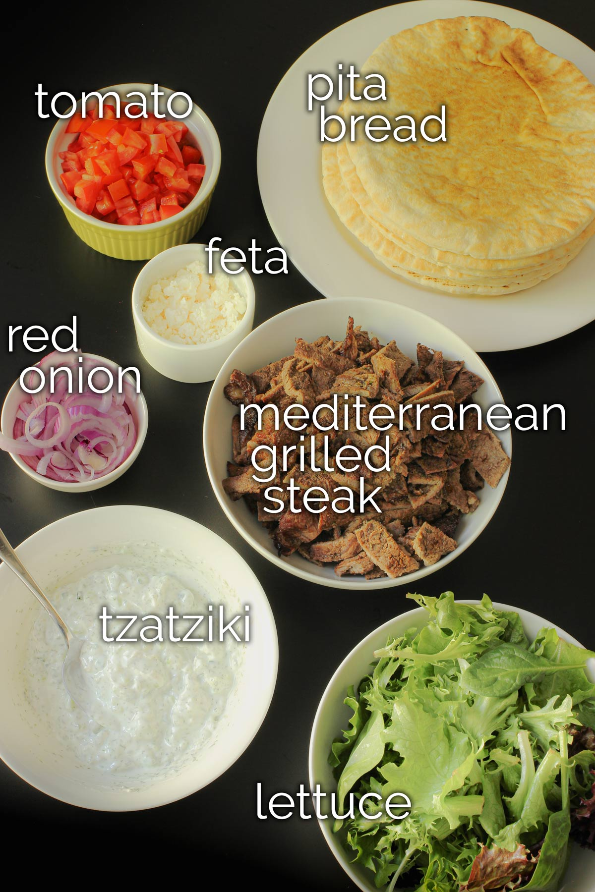 ingredients for greek pita sandwiches laid out on the table.