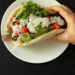 hand holding unwrapped steak pita sandwich with all the toppings.