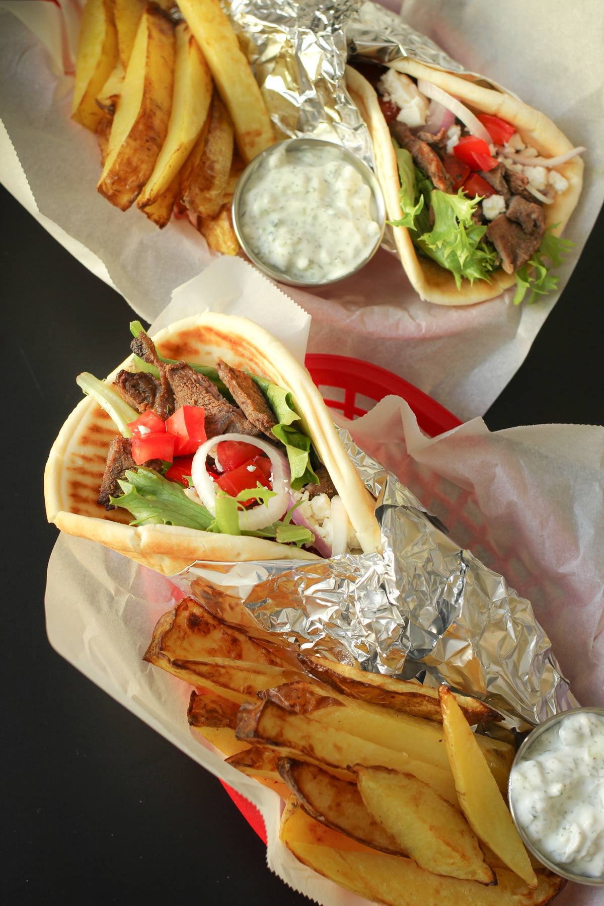 steak pitas in baskets with fries and cups of garlic yogurt sauce.