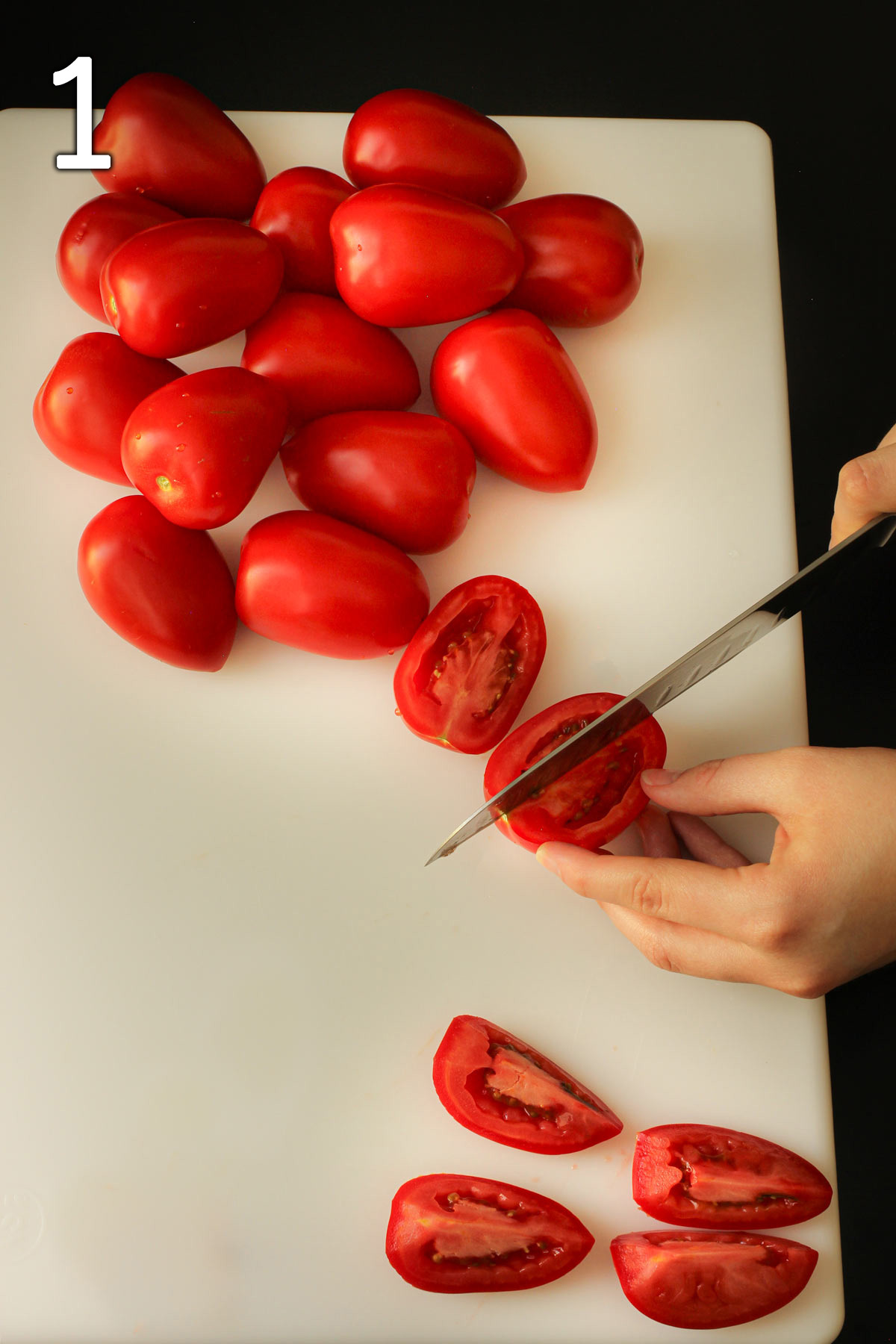 cutting tomatoes into quarters on a white cutting board.