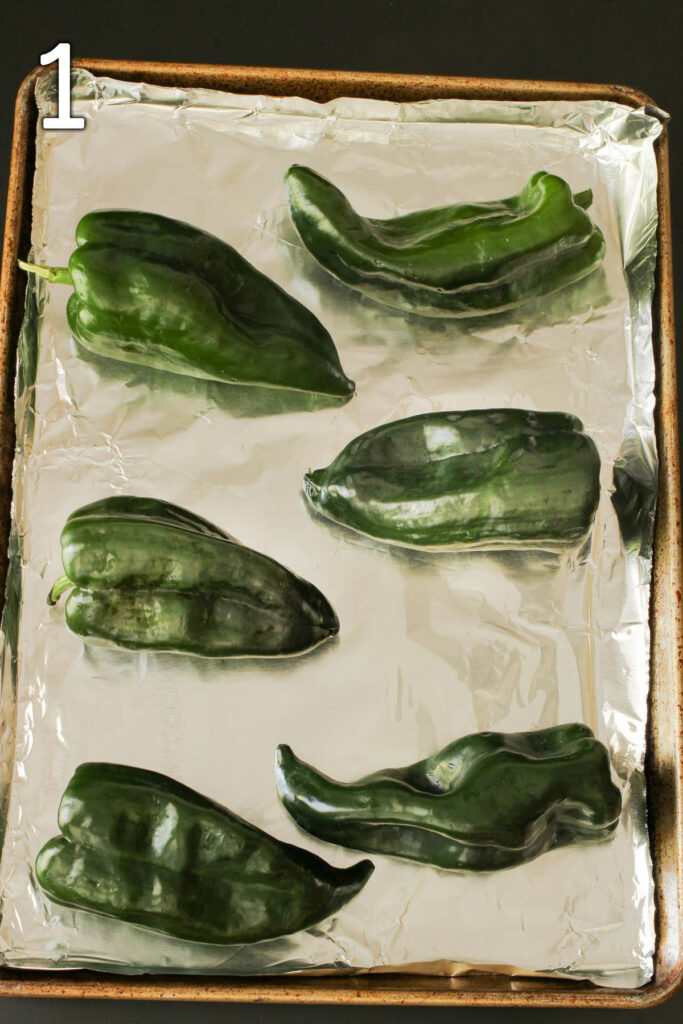 fresh poblano peppers laid out on a foil lined tray.