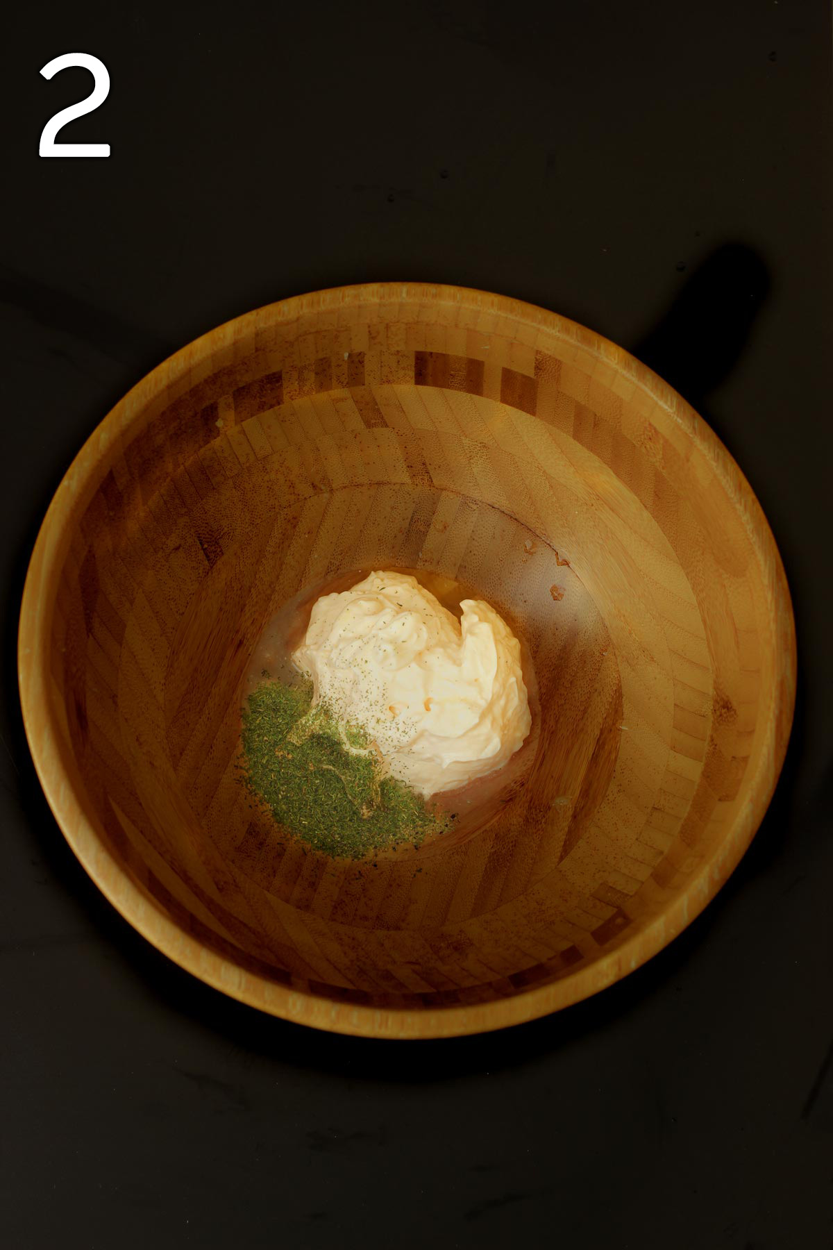 dressing ingredients in the bottom of a large wooden salad bowl.