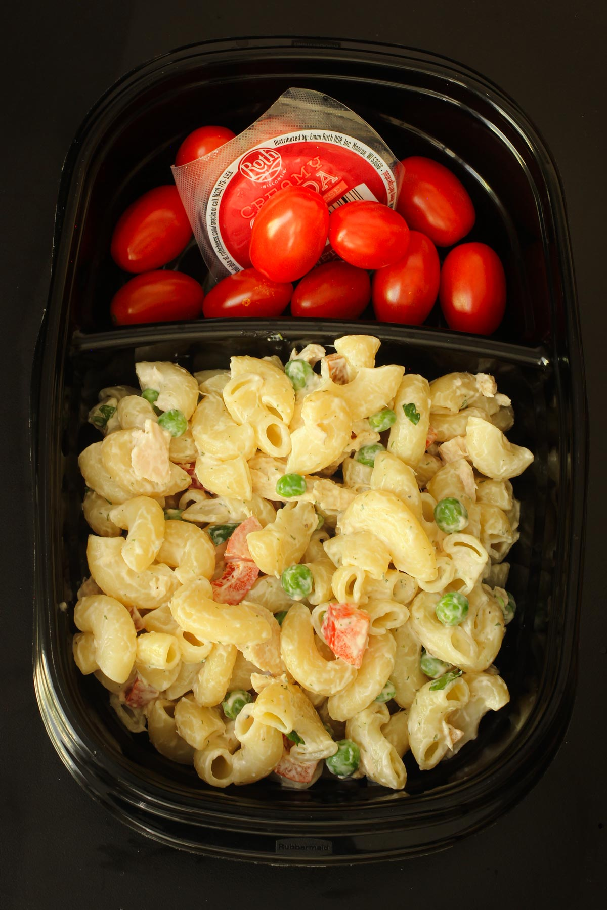tuna pasta salad in sectioned black meal prep dish with grape tomatoes and snacking cheese in other section.
