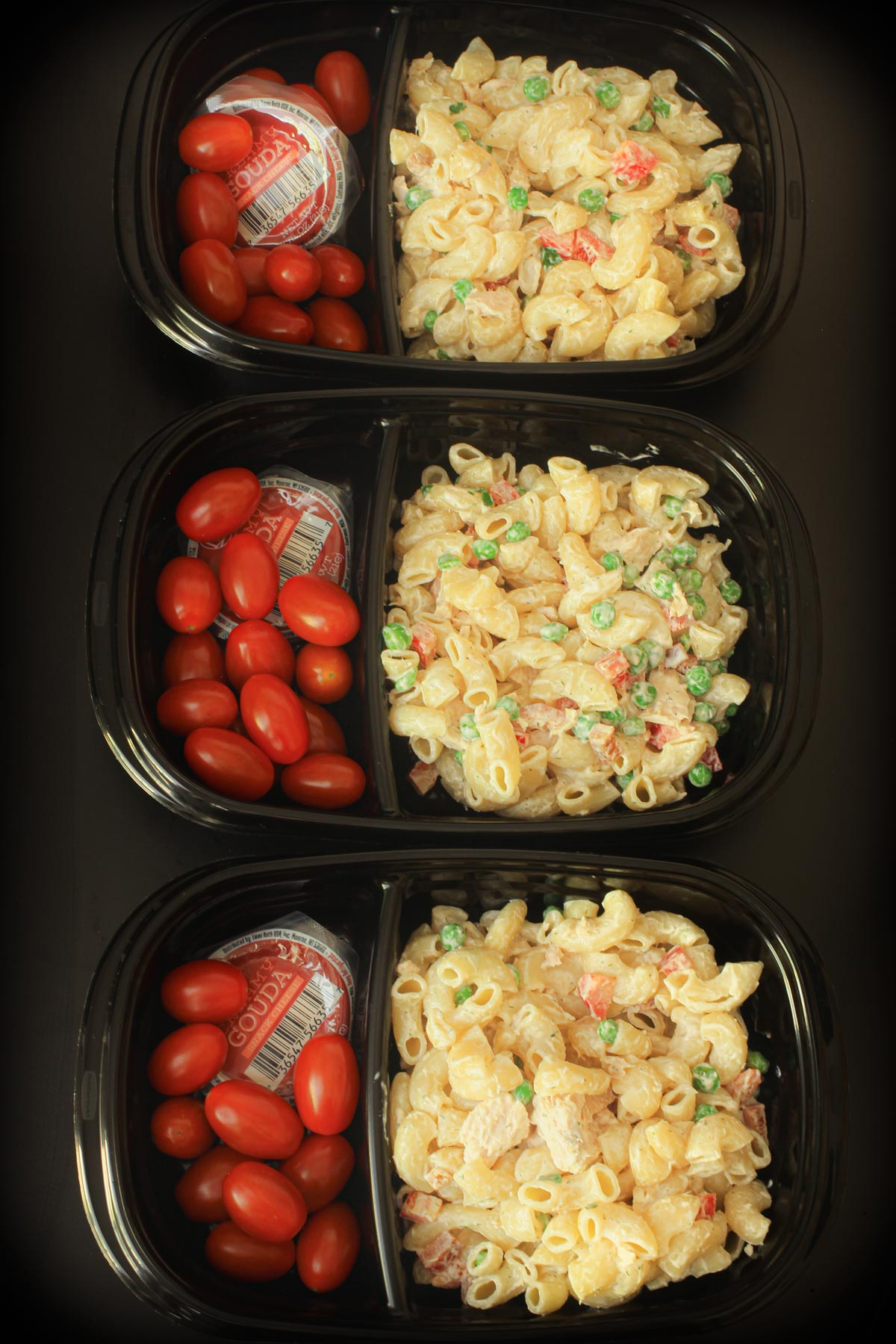 three black meal prep boxes packed with tuna mac salad, grape tomatoes, and snacking cheese.