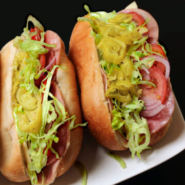 Italian sub sandwiches on platter bursting with cold cuts and other fillings.