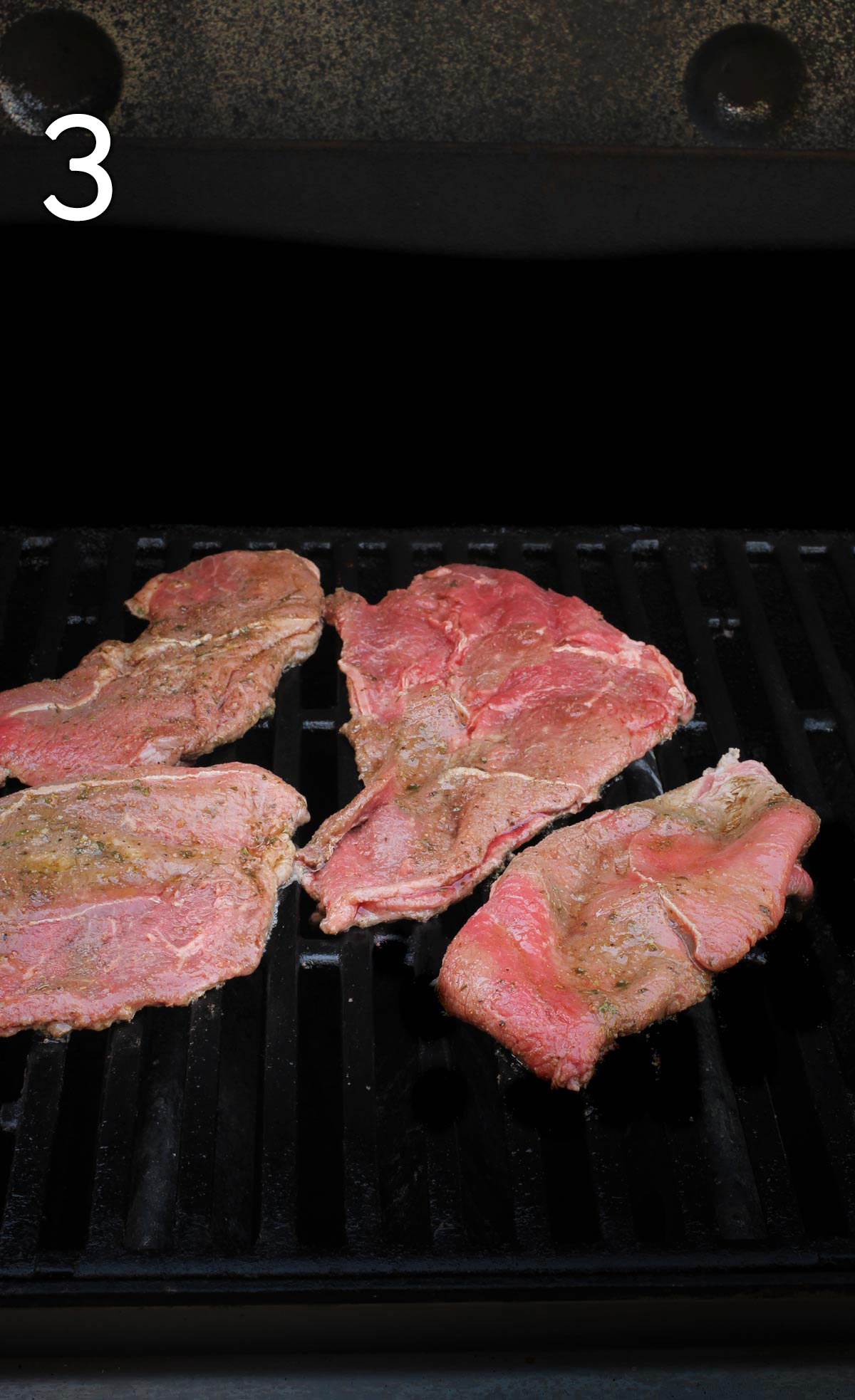 uncooked steak on hot grill.
