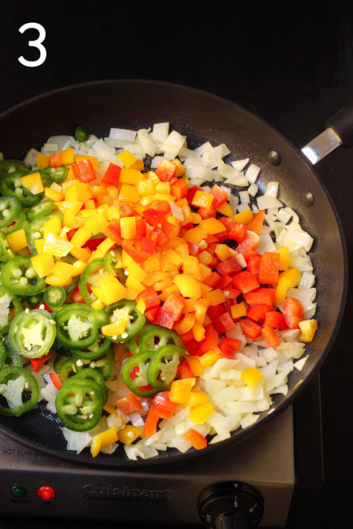 adding the peppers and chiles to the onions in the skillet.