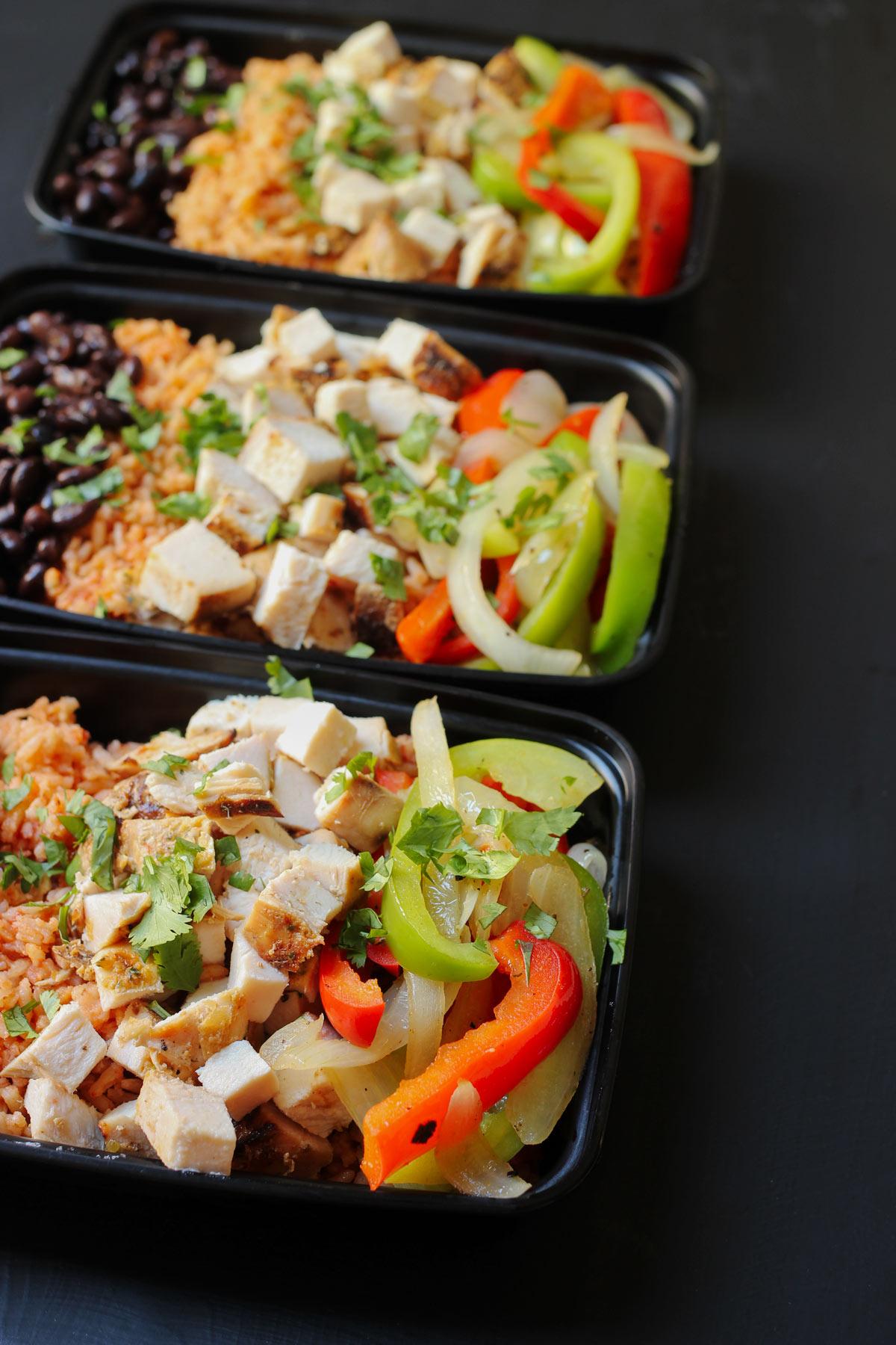meal prep boxes with fajita burrito bowls assembled.