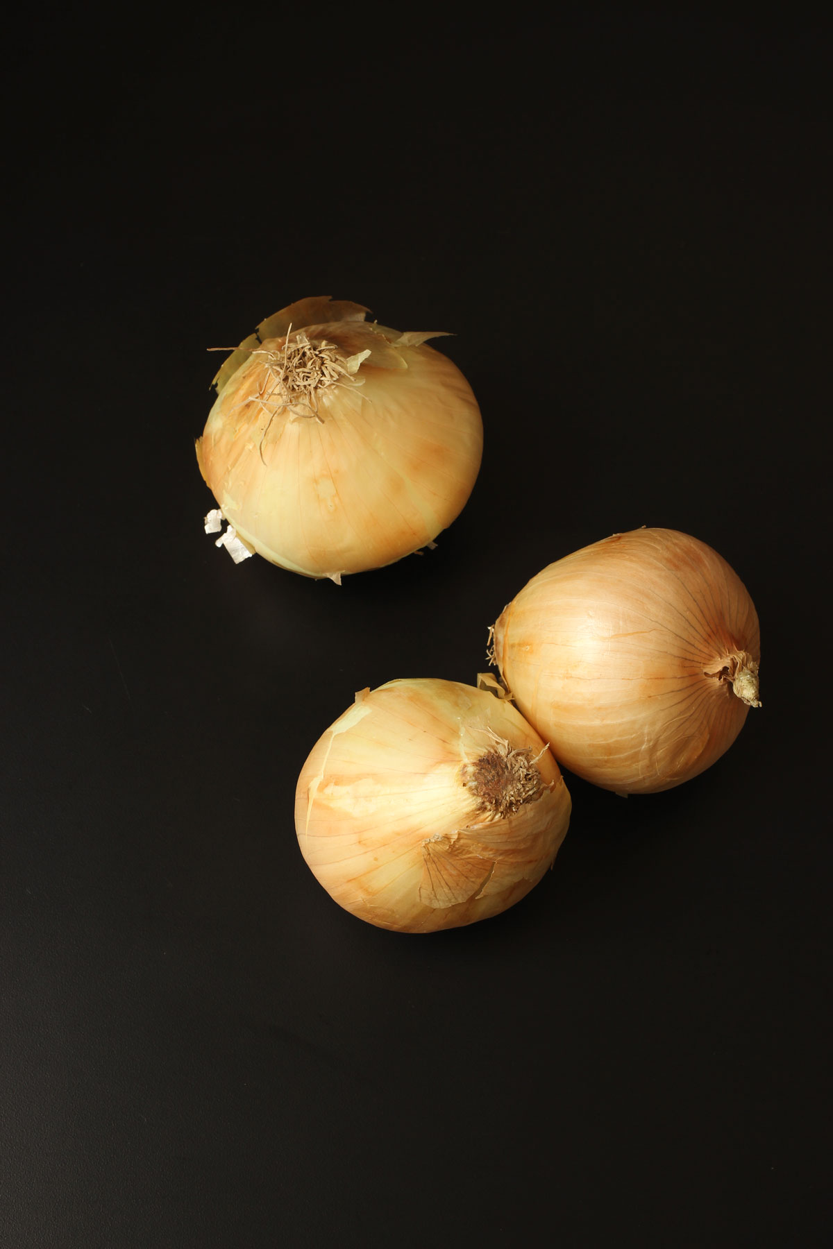three yellow onions on black table top.