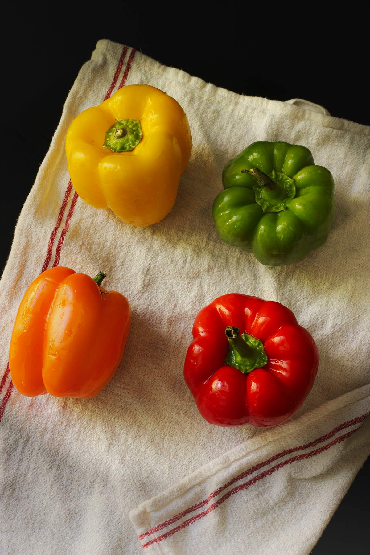 orange, yellow, green, and red bell peppers on a white tea towel.