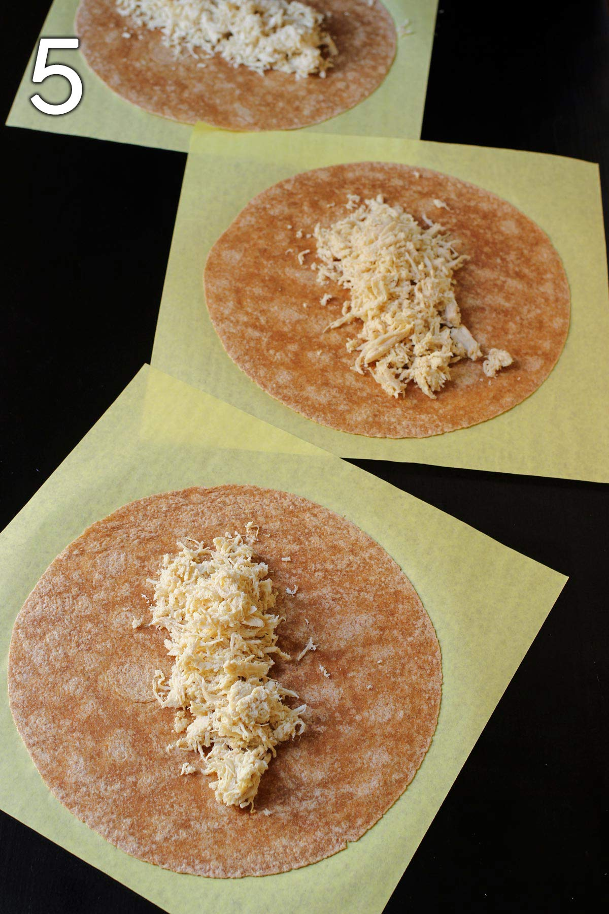 chicken distributed on whole wheat tortillas in assembly line.