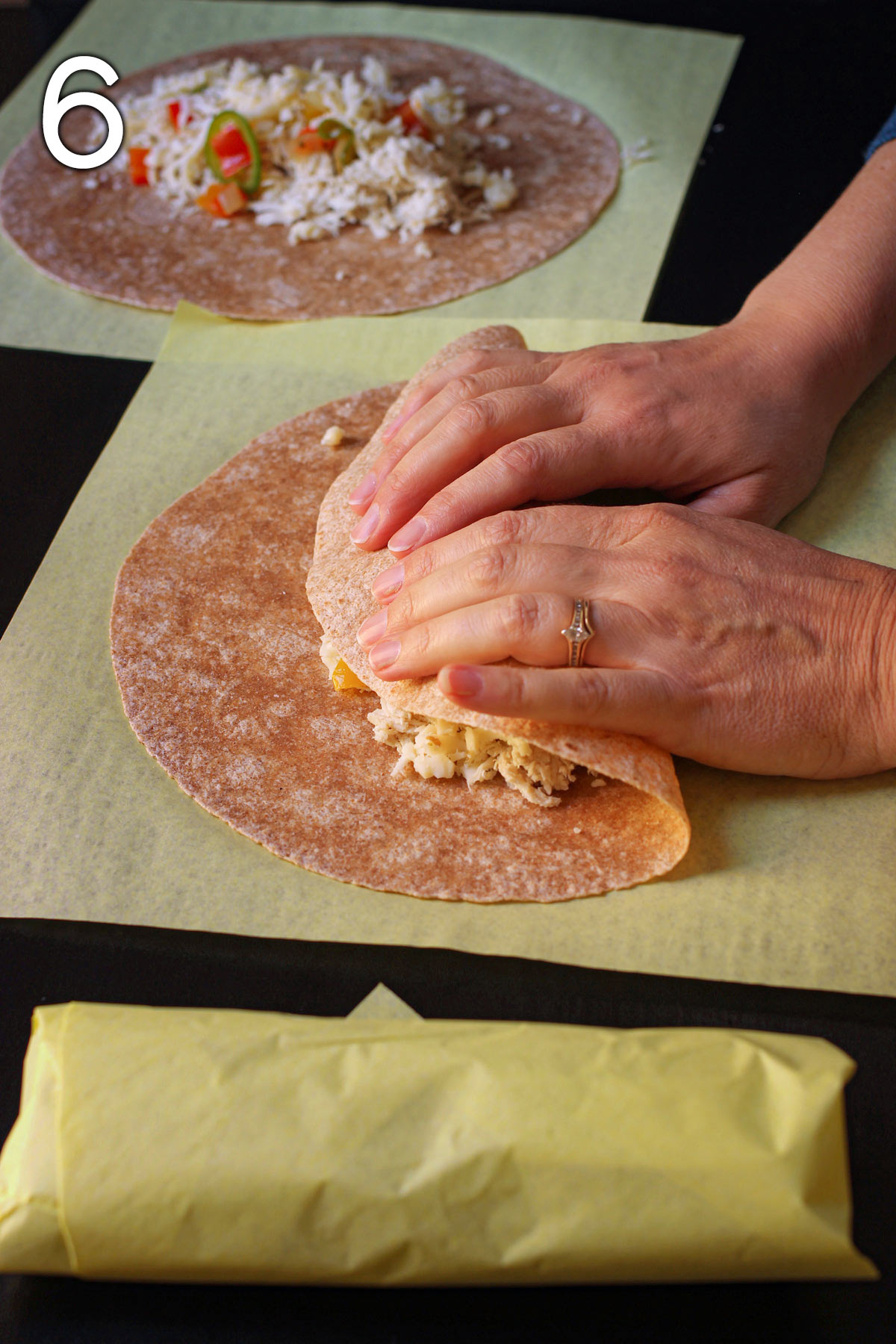 hand folding the bottom of the whole wheat tortilla over the filling of the burrito.