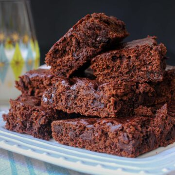 stack of brownies on square plate next to glass of milk and blue and white napkin.