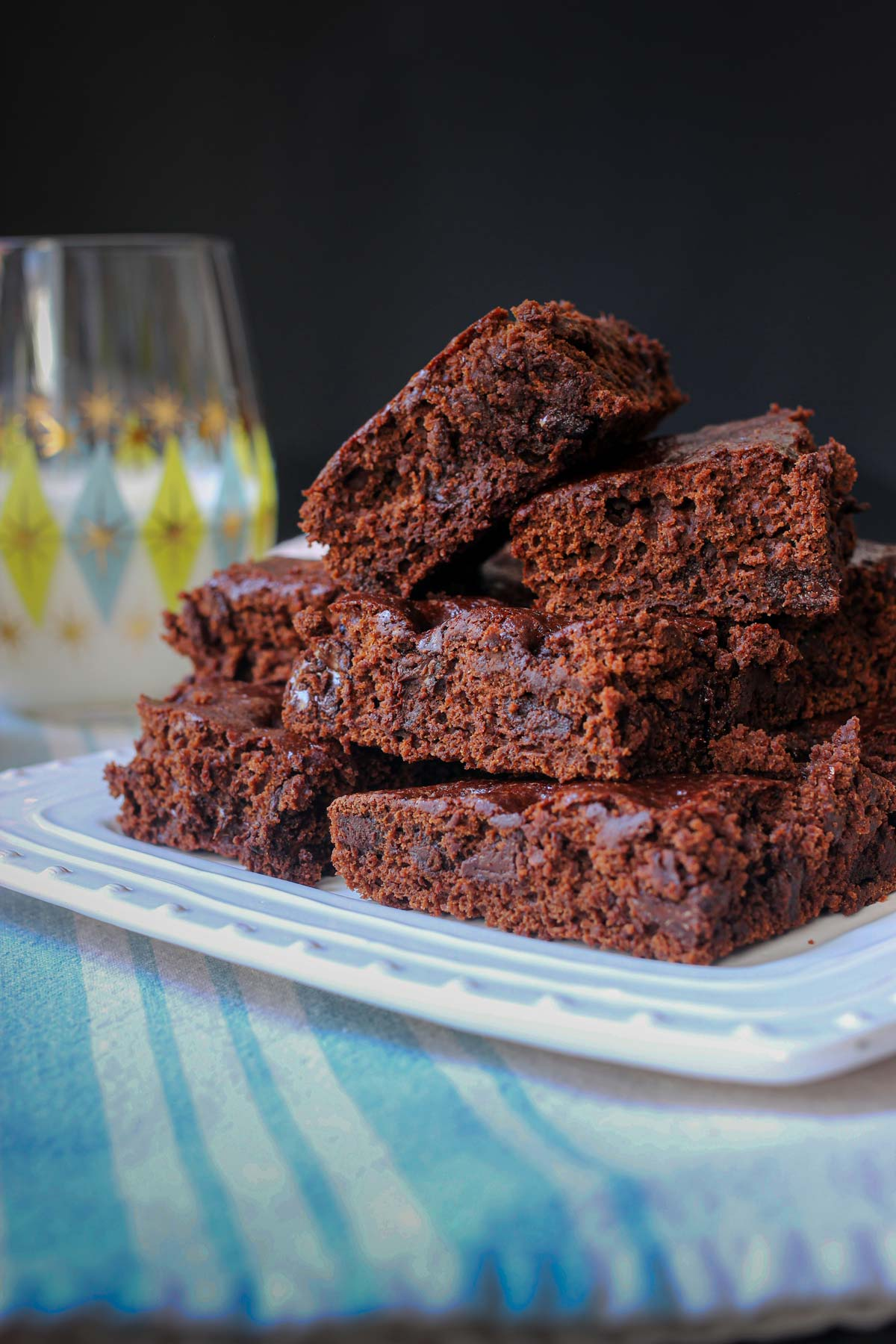 brownies stacked on white tray on blue napkin next to blue and green glass of milk.