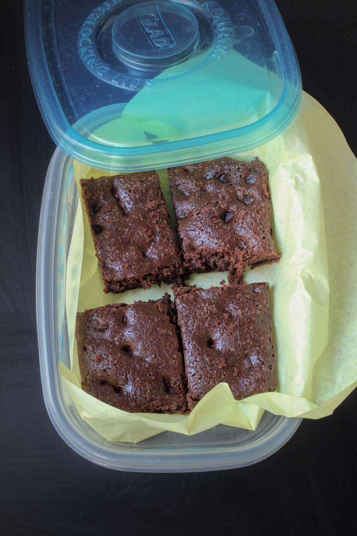 brownies sliced and arranged in a plastic container with a lid lined with deli wrap.