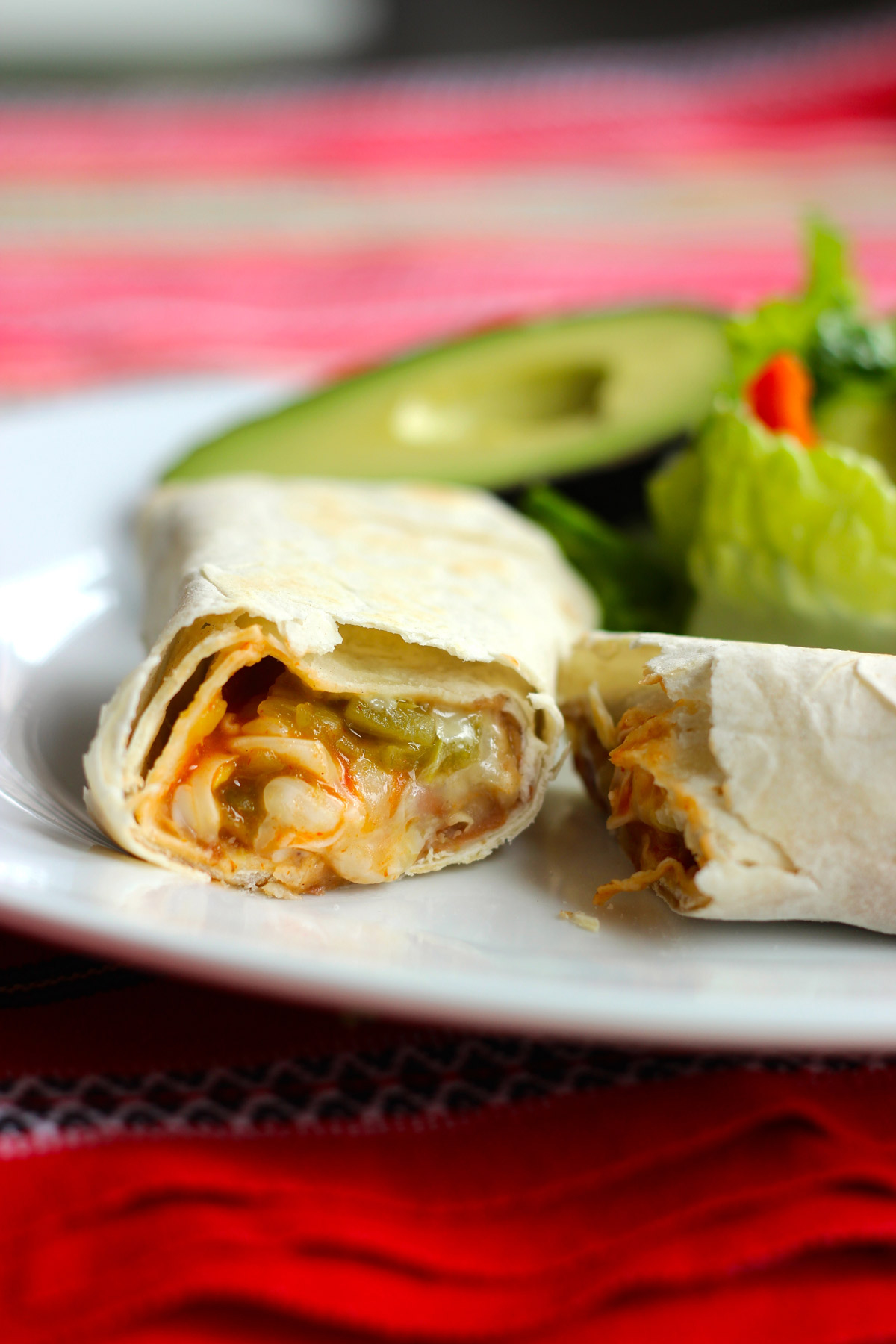 green chile burrito cut in halves on white plate with avocado and salad in background.