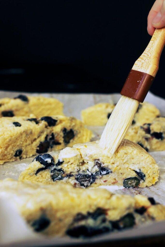 brushing extra cream on the cut scones.