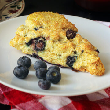 close up of a lemon blueberry scone on a white plate with a handful of fresh blueberries.