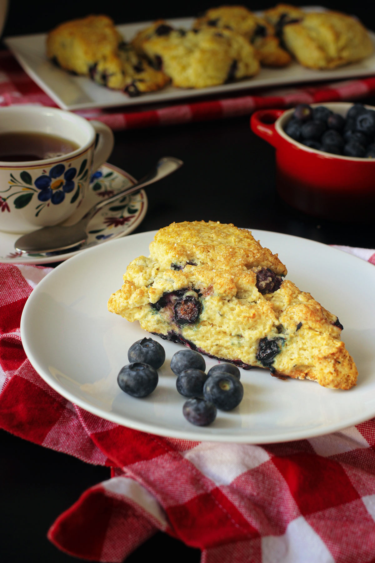 lemon blueberry scone on a plate with fresh blueberries atop a red checked napkin next to a cup of tea.