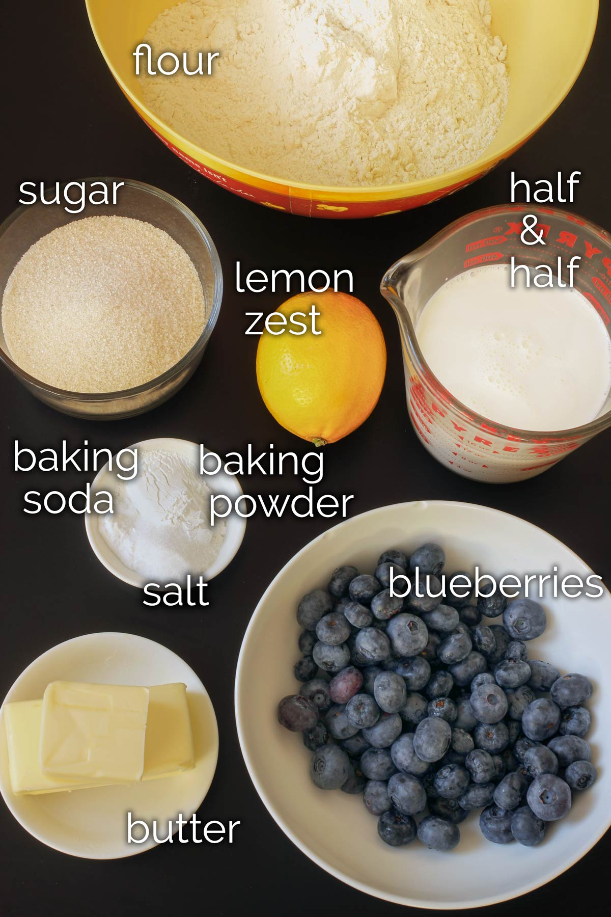 ingredients for lemon blueberry scones laid out on a black table top.