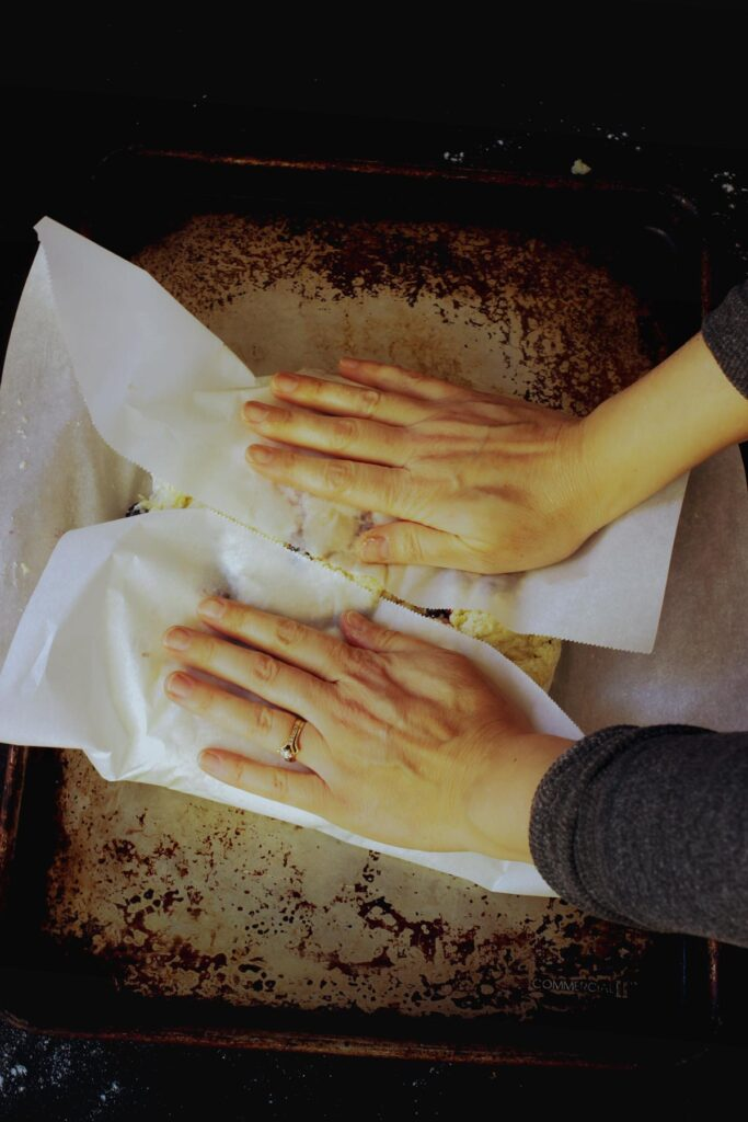 hands folding the parchment over the sticky dough to shape it into a round.
