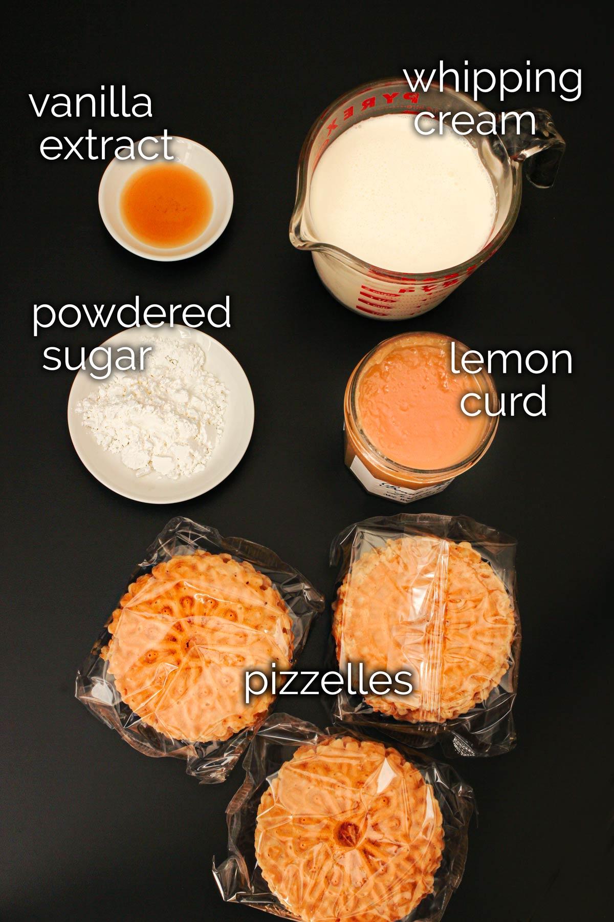 ingredients for lemon icebox cake on black background.