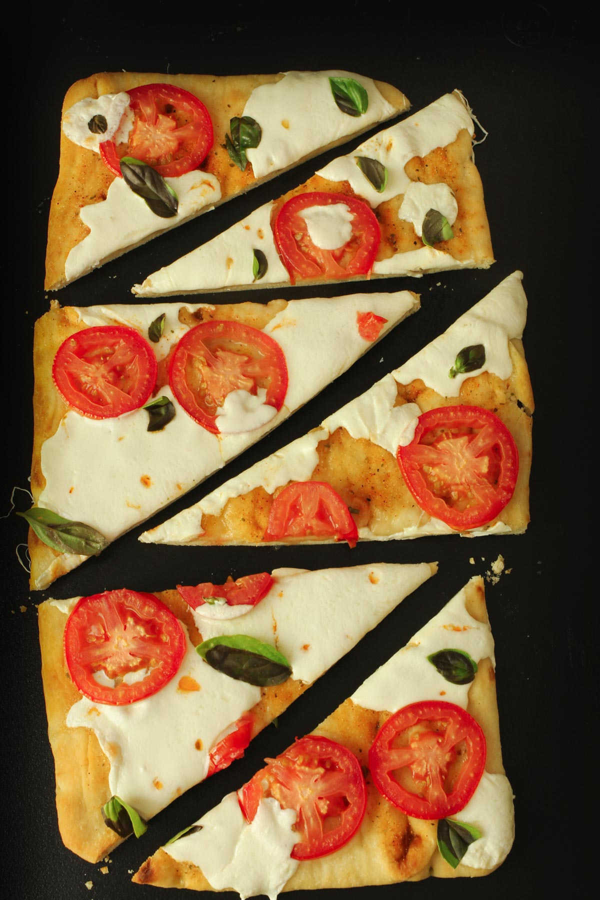 completed flatbread pizza sliced on black cutting board.