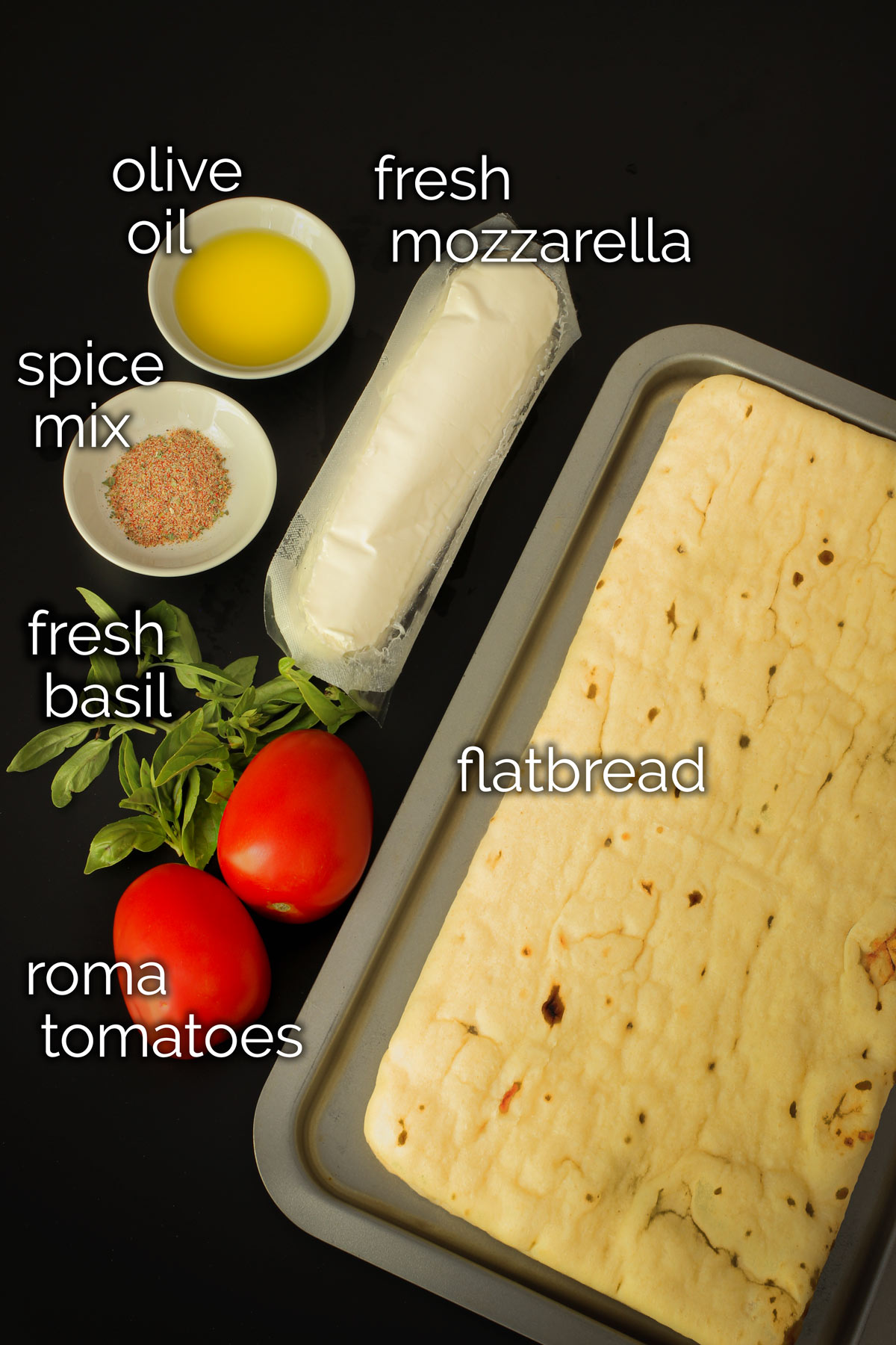 ingredients for margherita flatbread pizza laid out on black table top.